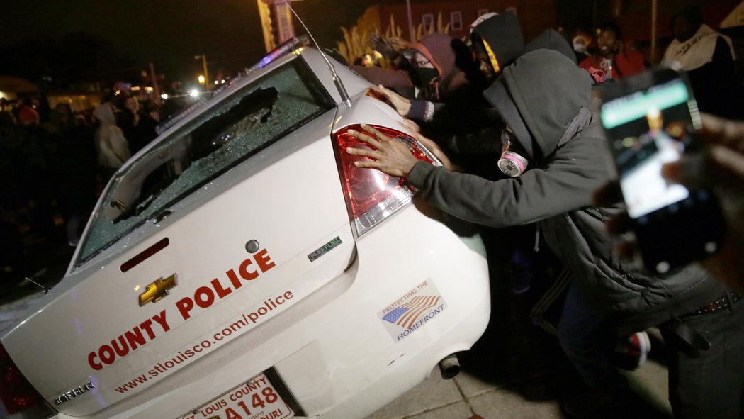 Protestors in Ferguson attempt to overturn police car (David Goldman/AP photo)